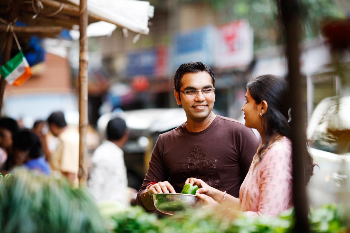 Indian man and woman talking at a vegetable stand in an outdoor market.