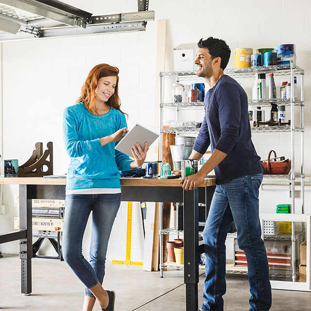 Happy man and woman talking while standing in a home garage and looking at a tablet