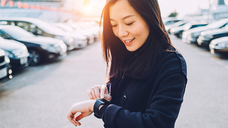 Woman standing in a parking lot looking at her watch.
