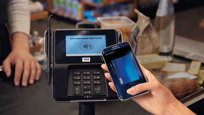 A hand holding a mobile phone showing a Visa card on the screen while in front of a payment terminal.
