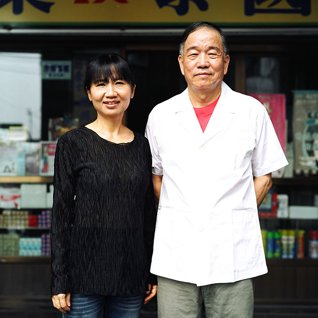 asian couple standing infront of a storefront